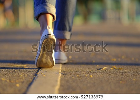Woman jeans and sneaker shoes walking on the road sunset light