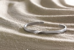 woman jewelry bracelet on white sand with moody sunset lighting