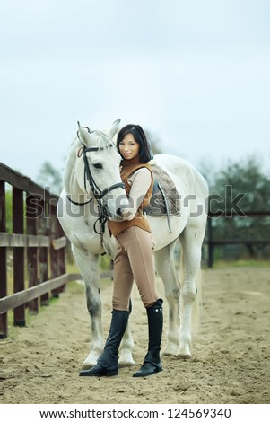 Woman jockey is riding the horse outdoor