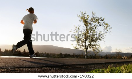 woman jogging along a river in the morning