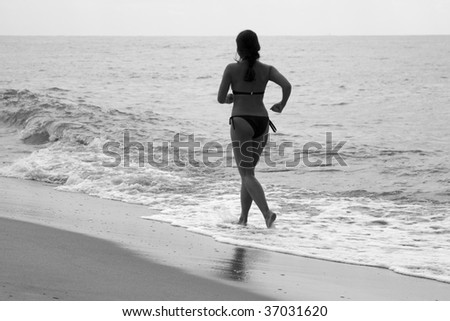 Woman jogging at the beach, black and white