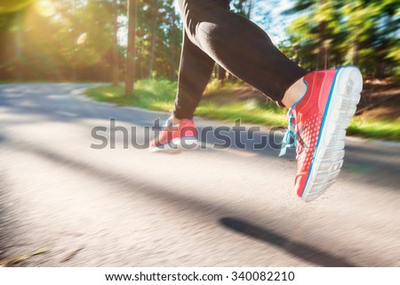 Woman jogging down an outdoor trail at sunset #340082210