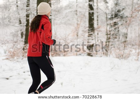 Woman jogging in winter forest