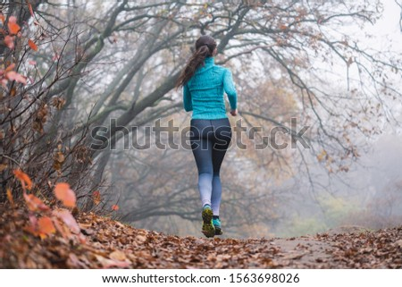 Woman jogging jumping in forest, no face. Fallen foliage on the ground, autumn foggy morning. Flying runner. Back view.