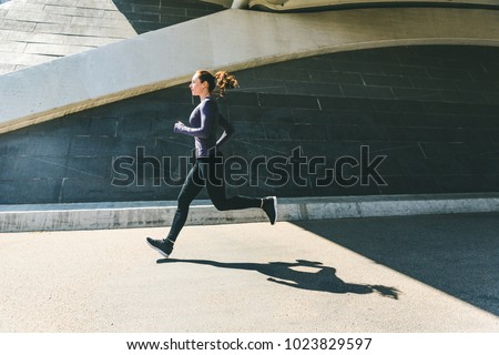 Woman jogging or running, side view with her shadow on the ground. Girl wearing sportswear doing fitness activities outdoors. Healthy lifestyle and sport concepts