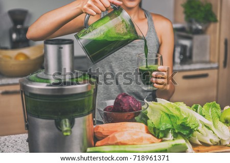 Photo of  Woman juicing making green juice with juice machine in home kitchen. Healthy detox vegan diet with vegetable cold pressed extractor to extract nutrients for smoothie drink.