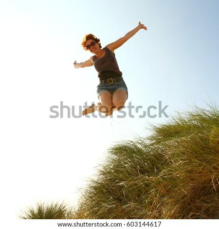 woman jumping for joy/jumping for joy/ woman jumping for joy #603144617