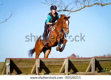 Woman jumping horse over a panel on cross country course