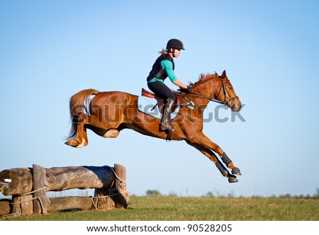 Woman jumping horse over log on cross country course