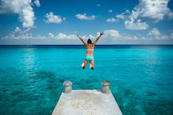 Woman jumping in blue water in tropical sea water from pier view back. Vacation in caribbean
