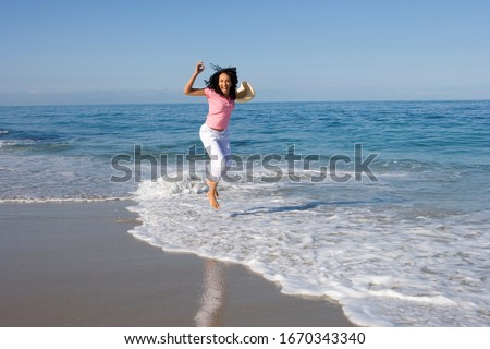 Woman jumping in waves on beach on summer vacation at camera