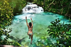 Woman jumping into amazing blue waterfall, in the middle of a forest