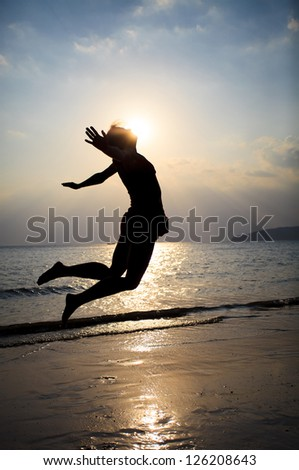 woman jumping on beach in sunset