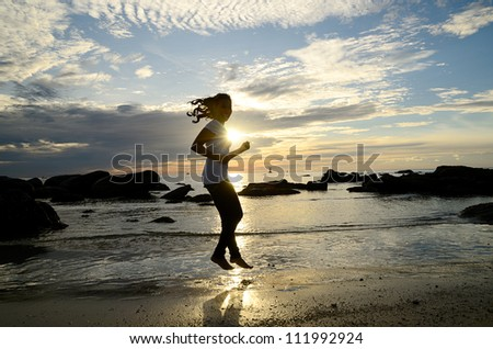 Woman jumping on the beach silhouetted the sunrise.