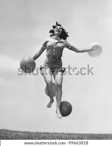 Woman jumping outside with balloons
