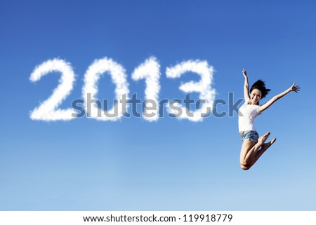 Woman jumping under clear blue sky with 2013 clouds next to her