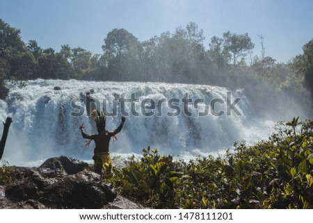 Woman jumping waterfall in indigenous village #1478111201