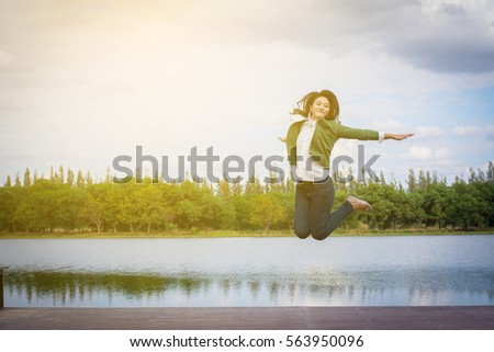 Woman jumps with arms raised on a bench by the pool. Сток-фото ©