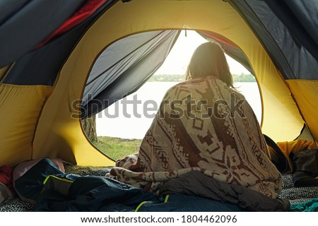 Woman just woken up in camping tent, wrapped in wool blanket and admiring sunrise on the river. Local travel on nature, trekking, camp lifestyle, outdoor gear. View from behind.  Foto stock ©