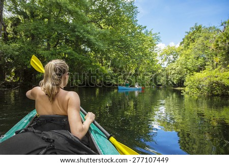Woman kayaker paddling down a beautiful jungle river with two people in a canoe on a gorgeous day. Lots of copy space and view from behind