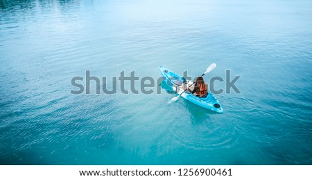 Woman kayaking isolatedly in the middle of the blue ocean