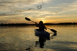 Woman kayaking on Lake Ontario at sunset with a flock of geese flying in the distance
