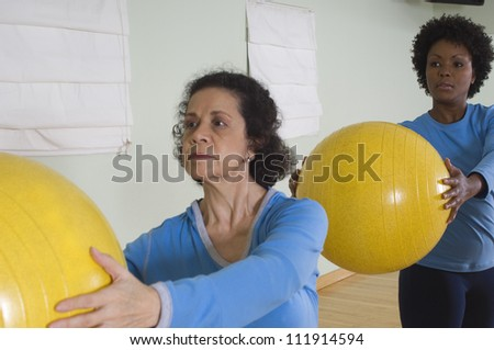 Woman keeping exercise balls in fitness class - stock photo