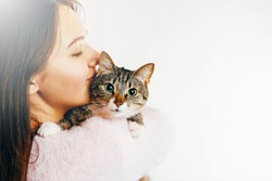 woman kisses beautiful cat, hugs cat,  cat and girl on white background