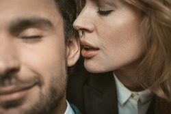 Woman kisses or whispers in man's ear. Selective focus on female lips near male ear in the center of image. Passionate couple in love. Close up shot.