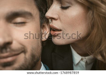 Woman kisses or whispers in man's ear. Selective focus on female lips near male ear in the center of image. Passionate couple in love. Close up shot. Photo stock ©