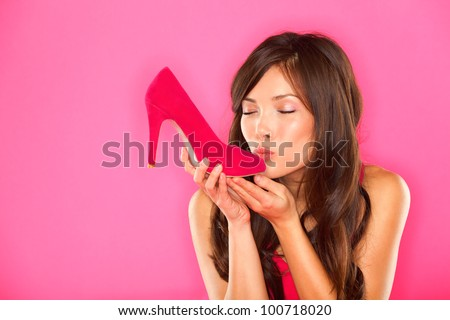Woman kissing shoe. Women loves shoes concept. Multiracial girl and pink high heels shoes on pink background. Beautiful young happy mixed race Asian Chinese and Caucasian female model.