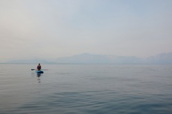 Woman kneeling on Paddle Board on Blue Waters of Lake Tahoe with Smoke Filled Sky from 2020 Wildfires