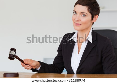 Woman knocking a gavel in her office