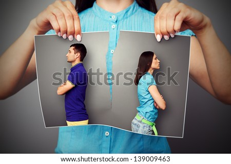 woman lacerating photo of young couple in quarrel over dark background