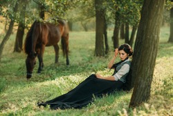 Woman lady princess. vintage black dress costume medieval clothes sits rests dreaming enjoy forest summer nature under tree sunny day. background walks brown animal horse. Fantasy photography quuen