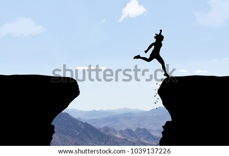 Woman landing after jumping over abyss.