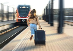 Woman late from train. Tourist running and chasing the leaving train in station. Person with stress pulling suitcase in platform. Rushing to get on.