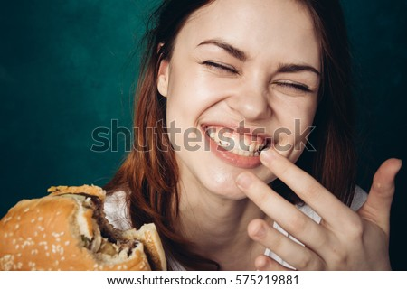 Woman laughing and eating a hamburger, hamburger and smile. #575219881