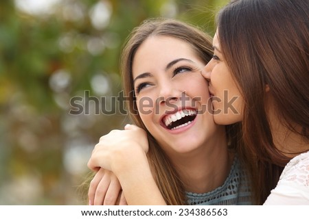 Woman laughing with perfect teeth while a friend is kissing her with a green background