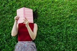 Woman lay down or relaxing on green grass reading book in summer or spring, top view