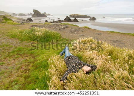 Woman lay on grass in Pacific ocean beach. #452251351