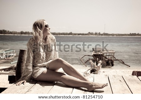 Woman laying at the wooden deck along the beach