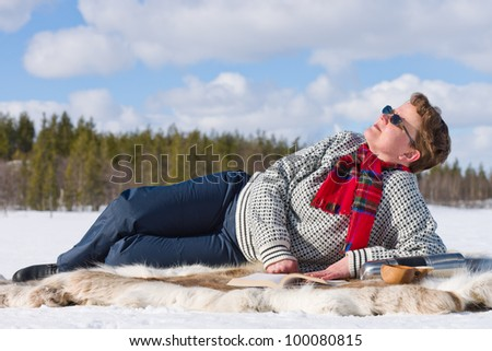 Woman laying down on the reindeer skin and enjoying the warm sun.