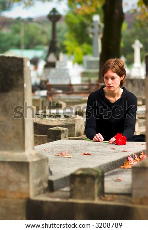 Woman Laying Flower on Grave in Cemetery
