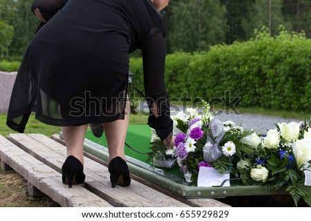 Woman laying flowers on a grave at a funeral