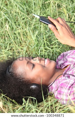 Woman laying in park listening to music