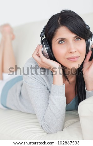 Woman laying on a couch while wearing headphones on in a living room