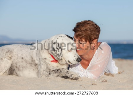 woman laying on beach with old rescue dog or pet