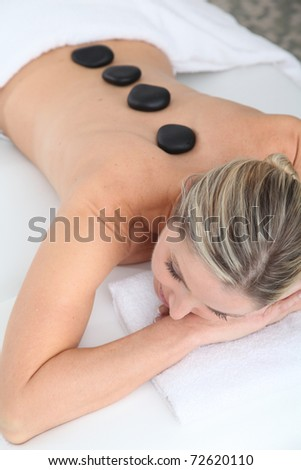 Woman laying on massage bed with hot stones on her back