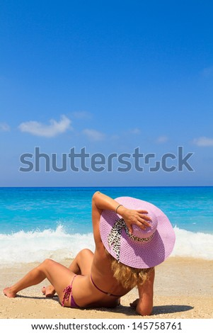 Woman laying on the beach in beach pink straw hat enjoying summer holidays looking at the ocean